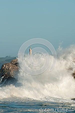 Grote golven tegen de rotsen De vuurtoren van Santander, Cantabrië, Spanje