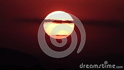 Grote heldere zon achter de wolken bij zonsondergang stock footage