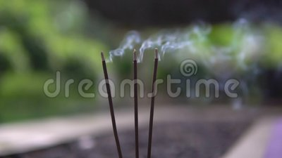 Ground angle, slow motion of incense sticks outside, spreading smell to  relax