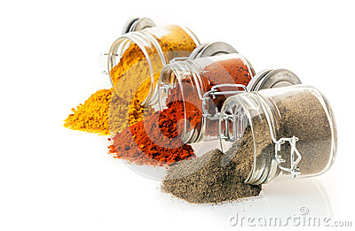 Ground spices spilling from glass jars