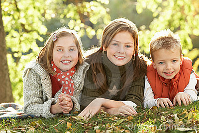 Group Of 3 Children Relaxing Outdoors In Autumn
