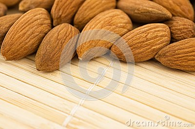 Group of almonds on a bamboo mat.