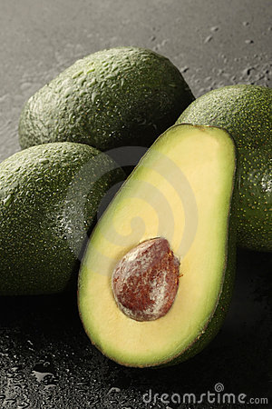 Group of avocado with half on black background