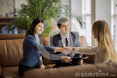 Group of business people congratulating their handshaking colleagues