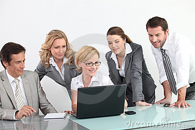 Group of business people in front of a laptop