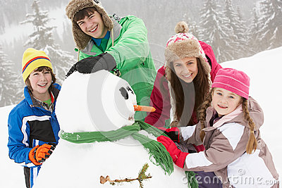 Group Of Children Building Snowman On Ski Holiday