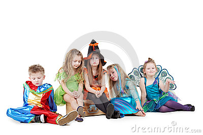 Group of children in masquerade costumes sits