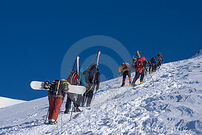 Group of climbers with skis and snowboards