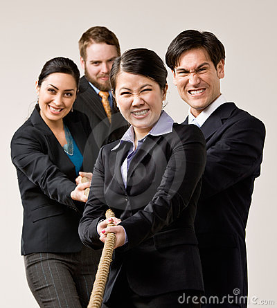 Group of co-workers pulling rope in tug-of-war