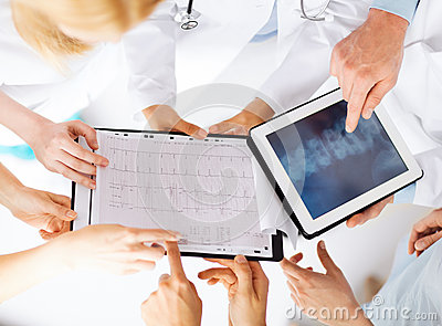 Group of doctors looking at x-ray on tablet pc