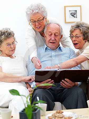 Group of elderly people looking at photographs