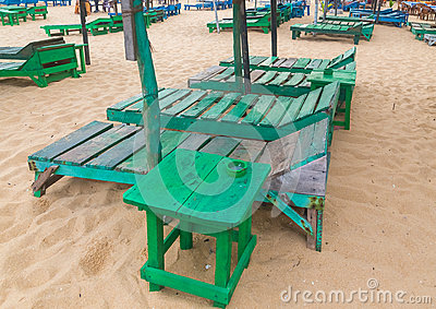 Group of empty green sunbeds at beach.