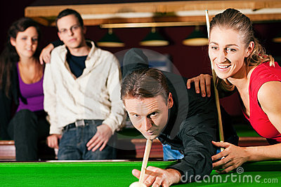 Group of four friends in a billiard hall playing s