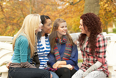 Group Of Four Teenage Girls Sitting And Chatting
