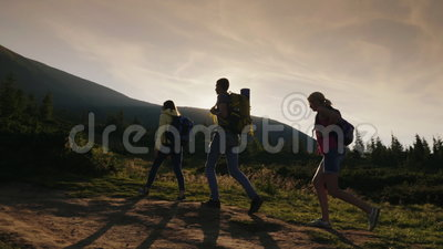 A group of friends with backpacks rises up the mountain. In the rays of the setting sun. Active lifestyle. 4K slow motion video stock video