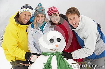 Group Of Friends Building Snowman