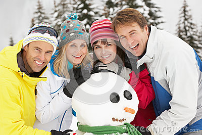Group Of Friends Building Snowman On Ski Holiday