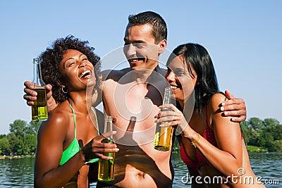 Group of friends drinking beer in swimwear