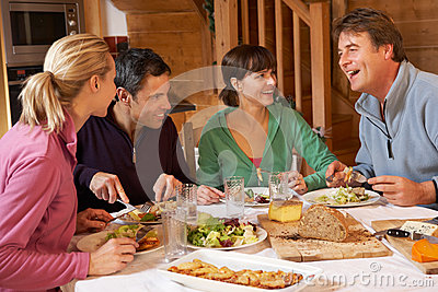 Group Of Friends Enjoying Meal In Alpine Chalet