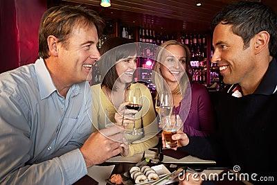 Group Of Friends Enjoying Sushi In Restaurant