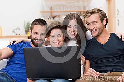 Group of friends laughing at a laptop