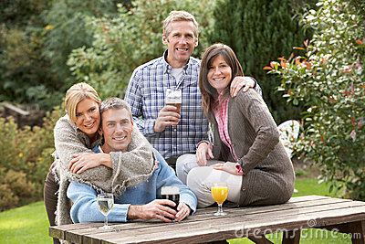 Group Of Friends Outdoors Enjoying Drink In Pub