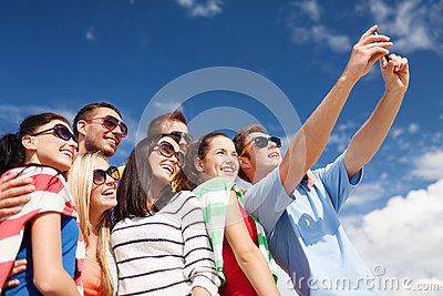Group of friends taking picture with smartphone
