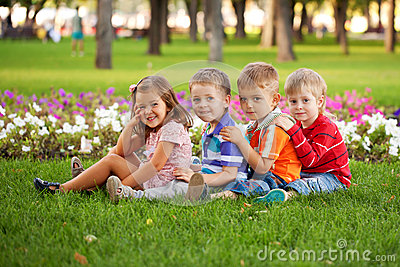 Group of fun children on the green grass.