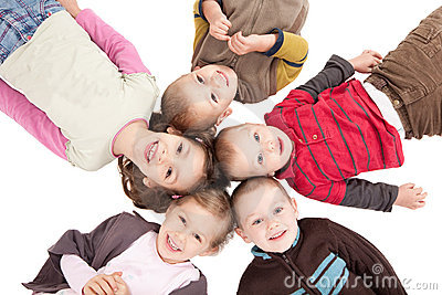 Group of happy kids lying on backs on floor