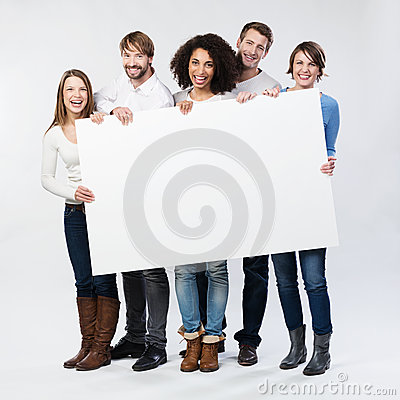 Group of happy young people with a blank sign