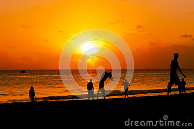 Group of happy young people jumping by the beach sunset