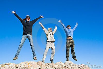Group of hikers jumping on mountain summit