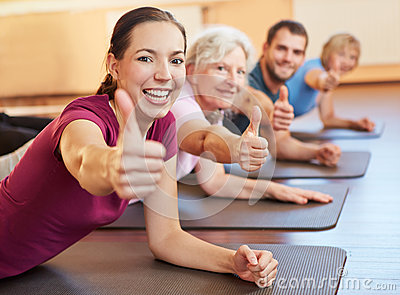 Group holding thumbs up in gym