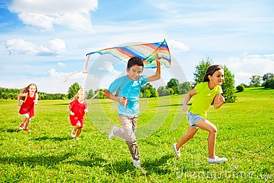 Group of kids run with kite