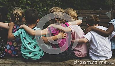 Group of kindergarten kids friends arm around sitting together Stock Photo
