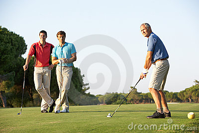 Group Of Male Golfers Teeing Off