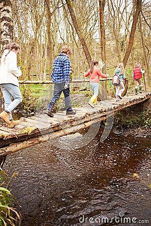 Free Group Of Children Crossing Stream On Wooden Bridge Royalty Free Stock Photo - 59776135