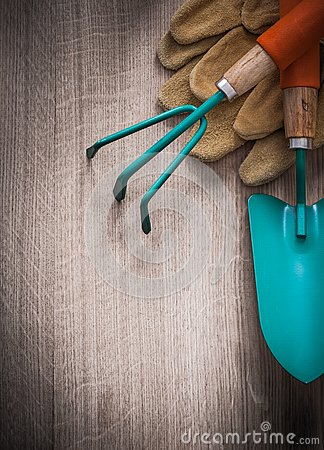Free Group Of Leather Gardening Gloves Hand Spade And Rake On Wooden Royalty Free Stock Images - 57539469
