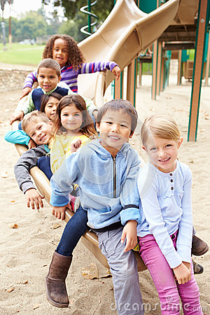 Free Group Of Young Children Sitting On Slide In Playground Royalty Free Stock Image - 54987456