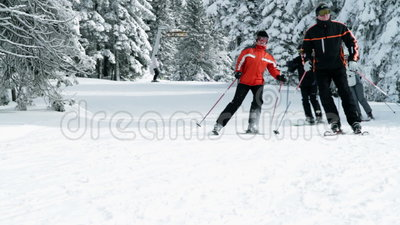 Group of older people enjoy skiing in winter. A group of people skiing and enjoying in the idyllic winter time soroundings
