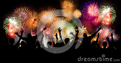 Group of people enjoying spectacular fireworks show in a carnival or holiday