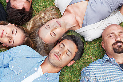 Group of people lying on grass taking a nap