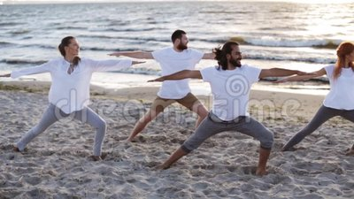 group of people making yoga exercises on beach stock video