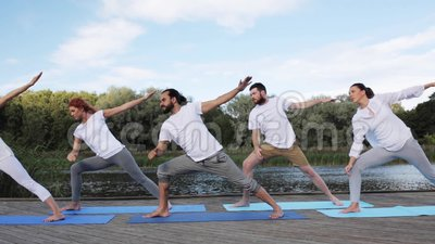 group of people making yoga exercises outdoors stock