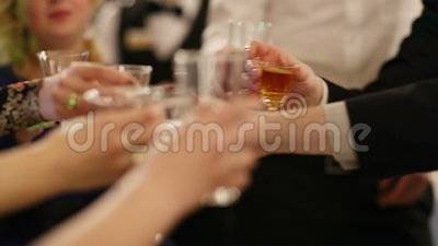Group of people toasting at a celebration. Clinking their glasses together in congratulations , close up view of their hands