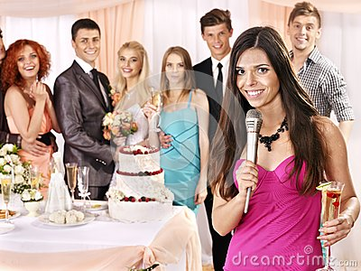 Group people at wedding singing song.