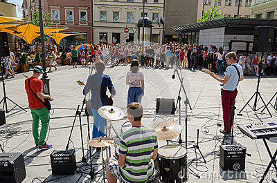 Group perform on street and people listen concert