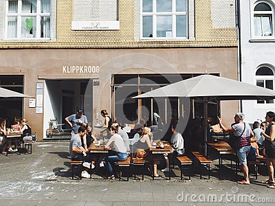Group Of Person Dining At Brown Wooden Outdoor Dining Set Beside Gray Concrete Building During Day Time Free Public Domain Cc0 Image