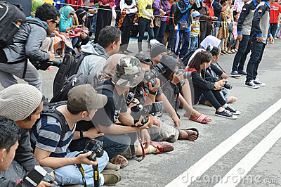 A group of photographers sitting in the street Editorial Stock Image