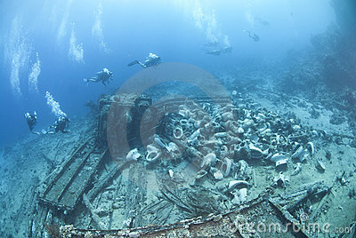 Group of scuba divers exploring a shipwreck.